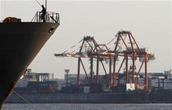 <p>A worker stands on a ship in front of a cargo ship at a port in Tokyo August 18, 2011. REUTERS/Toru Hanai</p>