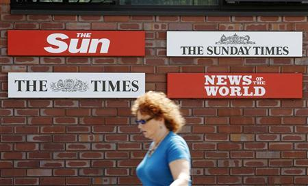 A woman passes signs outside the News International headquarters in London July 9, 2011. REUTERS/Luke MacGregor