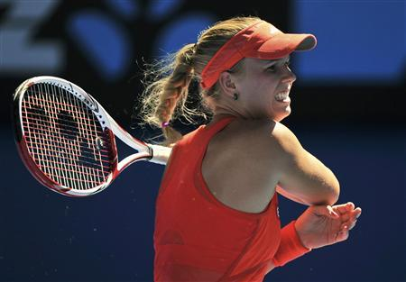 Caroline Wozniacki of Denmark hits a return to Kim Clijsters of Belgium during their women's singles quarter-finals match at the Australian Open tennis tournament in Melbourne January 24, 2012. REUTERS/Toby Melville