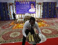 <p>A waiter serves snacks to the media as a picture of Mayawati, the chief minister of the northern Indian state of Uttar Pradesh, is seen in the background before her news conference in Lucknow January 15, 2012. REUTERS/Adnan Abidi</p>