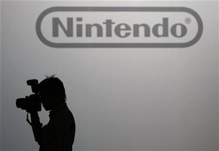 A photographer takes pictures in front of the logo of Nintendo Co Ltd at its news conference in Tokyo October 2, 2008. REUTERS/Kim Kyung-Hoon
