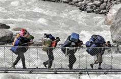 <p>Porters walk across a bridge over the Bhote Koshi river in the Everest region May 29, 2007. REUTERS/Shruti Shrestha</p>