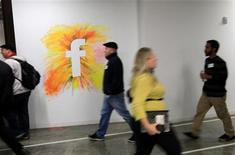 <p>Employees walk past the company logo at the new headquarters of Facebook in Menlo Park, California January 11, 2012. REUTERS/Robert Galbraith</p>