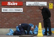 <p>Workers clear a drain at the entrance to News International's newspaper headquarters in Wapping, East London, November 23, 2011. REUTERS/Andrew Winning</p>