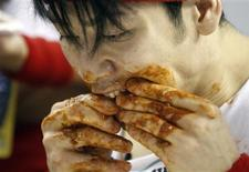 "<p>Competitive eater Takeru Kobayashi from Japan eats chicken wings on his way to winning ""Wingbowl 20"", the annual chicken wing eating contest in Philadelphia, Pennsylvania, February 3, 2012. REUTERS/Tim Shaffer</p>"