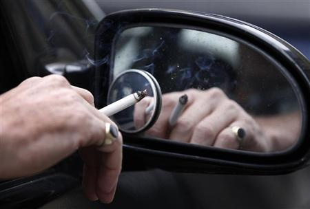A man smokes a cigarette as he sits in his car in Liverpool, northern England November 16, 2011. REUTERS/Phil Noble