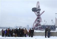 <p>Tourists look at the London 2012 Olympic Games site in east London on February 5, 2012. REUTERS/Olivia Harris</p>