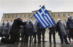 <p>Manifestation contre l'austérité devant le parlement grec à Athènes. La réunion des dirigeants politiques grecs prévue ce mardi pour valider les réformes exigées par les bailleurs de fonds d'Athènes en échange d'un deuxième plan d'aide a été repoussée à mercredi. Ce report serait lié au fait que les dirigeants des formations politiques n'ont pas encore reçu le texte du projet d'accord sur ce plan de renflouement de 130 milliards d'euros. /Photo prise le 7 février 2012/REUTERS/Yannis Behrakis</p>
