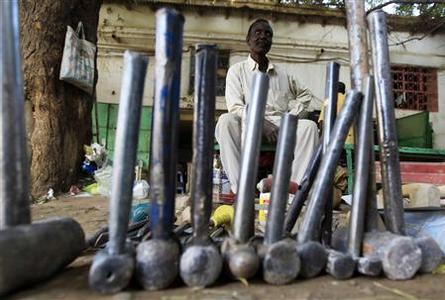 A skilled worker is seen sitting behind tools as he waits for customers at a market in Khartoum, January 7, 2012. REUTERS-Mohamed Nureldin