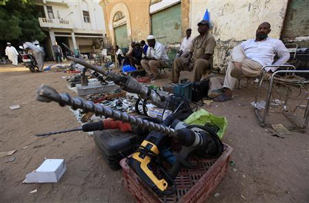 Skilled workers are seen sitting behind power tools as they wait for customers at a market in Khartoum, January 7, 2012. REUTERS-Mohamed Nureldin