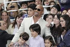 "<p>Actor Dwayne Johnson poses with fans after his arrival on the red carpet event to promote his new movie ""Journey 2: The Mysterious Island"" in Mexico City January 28, 2012. REUTERS/Henry Romero</p>"