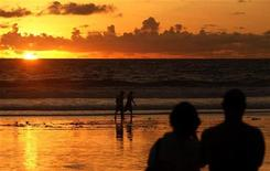 <p>Tourists watch the sunset from Kuta beach in Indonesia's resort island of Bali February 2, 2010. REUTERS/Murdani Usman</p>