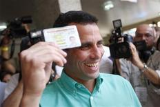 <p>Opposition presidential candidate and Miranda state Governor Henrique Capriles smiles as he arrives to cast his vote at a polling station in Caracas February 12, 2012. REUTERS/Carlos Garcia</p>