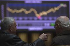 <p>Traders talk in front of a screen showing an index at Madrid's Bourse February 14, 2012. REUTERS/Sergio Perez</p>