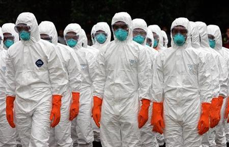 Livestock officials dressed in bird flu protective gear demonstrate for a new method of culling poultry by using carbon dioxide gas at a farm in Ayutthaya, north of Bangkok, August 19, 2004. REUTERS/Sukree Sukplang