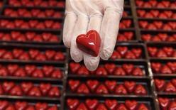 <p>Un empleado muestra un praliné con forma de corazón con motivo del día de San Valentín en una tienda de la chocolatería Wittamer en Bruselas, feb 14 2012. Casi dos tercios de los casados y de la gente que tiene alguien importante en su vida dicen que su pareja es la principal fuente de felicidad en sus vidas, según un nuevo sondeo mundial difundido el día de San Valentín. REUTERS/Francois Lenoir</p>