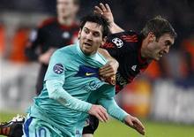 <p>Lionel Messi accroché par un défenseur du Bayer Leverkusen lors du match aller des huitièmes de finale de la Ligue des champions, mardi soir. Deux joueurs du club allemand ont mis aux enchères le maillot cédé par l'Argentin après la rencontre, provoquant la colère de leur directeur sportif. /Photo prise le 14 février 2012/REUTERS/Kai Pfaffenbach</p>