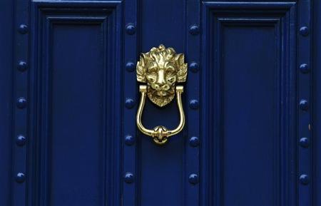 A brass door knocker is pictured on a blue door in London August 30, 2011. REUTERS/Luke MacGregor