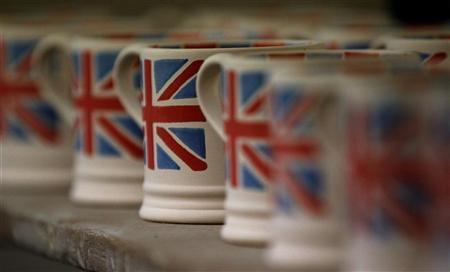 Mugs with Union flags painted on them wait to be fired as part of the Diamond Jubilee Collection at the Emma Bridgewater pottery factory in Stoke-On-Trent, central England February 24, 2012. REUTERS/Phil Noble