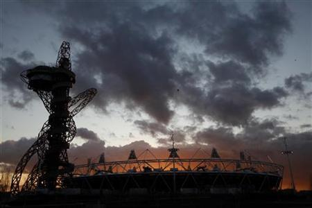 The sun sets behind the Olympic stadium and Anish Kapoor's ArcelorMittal Orbit in Stratford, east London, March 7, 2012. REUTERS/Andrew Winning