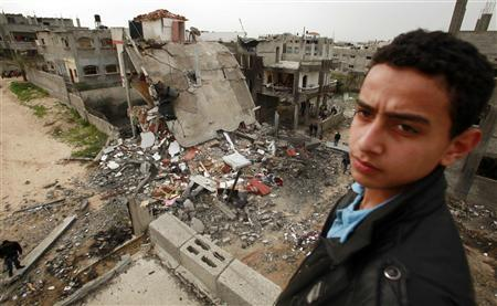 A Palestinian youth stands near a destroyed building after an Israeli air strike in Jabalya in the northern Gaza Strip March 12, 2012. REUTERS/Suhaib Salem