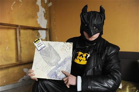 Zoltan Kohari, known as the Slovak Batman, poses with a portrait of himself in his home in the town of Dunajska Streda, some 34 miles (55 km) south of Bratislava March 8, 2012. REUTERS/Radovan Stoklasa