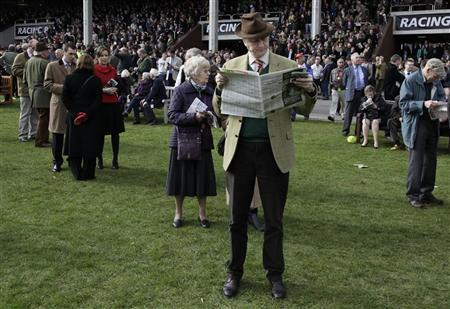 A race-goer reads a racing paper during the Cheltenham Festival horse racing meet in Gloucestershire, March 13, 2012. REUTERS/Stefan Wermuth
