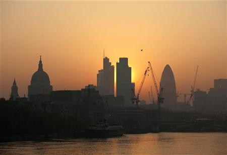 The sun rises above the financial district of the City of London April 23, 2011. REUTERS/Kieran Doherty