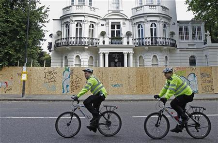 Police officers on bicycles pass a boarded-up house ahead of the annual Notting Hill Carnival in central London August 28, 2011. REUTERS/Luke MacGregor
