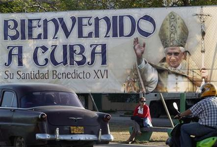 A woman sits under a banner of Pope Benedict XVI in Havana March 23, 2012. Pope Benedict said on Friday communism no longer works in Cuba and the Church was ready to help the island find new ways of moving forward without ''trauma''. The banner reads ''Welcome to Cuba''. REUTERS/Enrique de la Osa