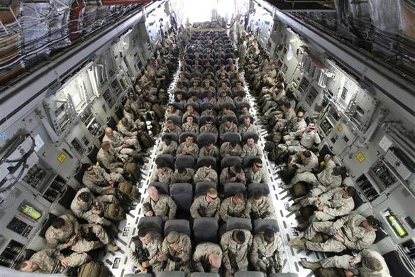 U.S. servicemen sit after boarding a transport plane before leaving for Afghanistan at the U.S. transit center at Manas airport near Bishkek, Kyrgyzstan, March 27, 2012. REUTERS-Vladimir Pirogov