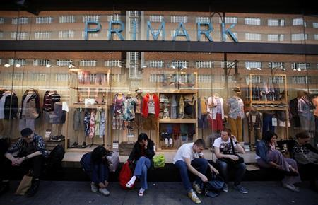 Shoppers sit outside Primark on Oxford Street, in central London, March 27, 2012. REUTERS/Andrew Winning