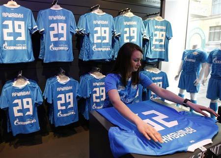 An employee smoothens a soccer jersey of Zenit St. Petersburg's Andrei Arshavin at a shop in St. Petersburg February 28, 2012. REUTERS/Alexander Demianchuk