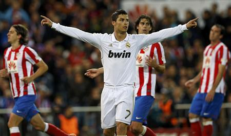 Real Madrid's Cristiano Ronaldo celebrates after scoring his third goal during their Spanish first division soccer match against city rivals Atletico Madrid at the Vicente Calderon stadium in Madrid April 11, 2012. REUTERS/Juan Medina