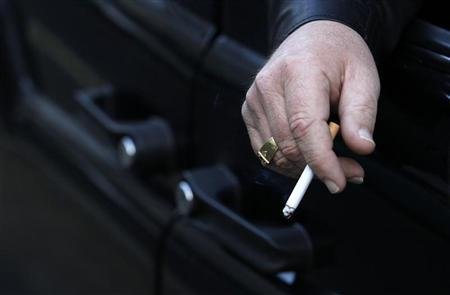 A man smokes in his car in London November 16, 2011. REUTERS/Suzanne Plunkett