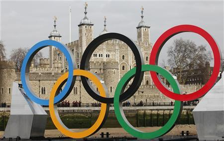 Yeomen Warders, also known as Beefeaters, are seen through Olympic rings mounted on a barge, as it is positioned in front of the Tower of London during a promotional event for the London 2012 Olympic Games, on the River Thames in London. REUTERS/Andrew Winning
