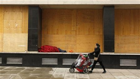 A pedestrian pushes a buggy past a person sleeping rough in an alcove of the recently vacated Westminster Magistrates Court in London January 20, 2012. REUTERS/Suzanne Plunkett