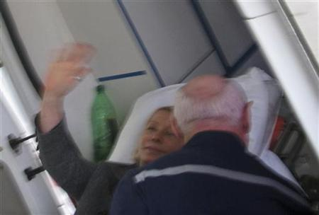 Former Ukrainian Prime Minister Yulia Tymoshenko waves from a stretcher as she is being transported to an ambulance in Kharkiv, April 22, 2012. REUTERS/Stringer