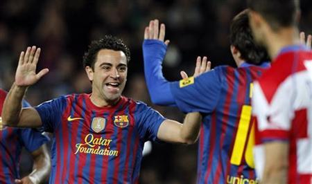 Barcelona's Xavi Hernandez celebrates a goal against Granada during their Spanish First division soccer match at Camp Nou stadium in Barcelona, March 20, 2012. REUTERS/Albert Gea