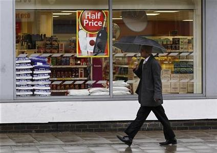 A pedestrian walks past a Tesco store in London April 18, 2012. REUTERS/Suzanne Plunkett