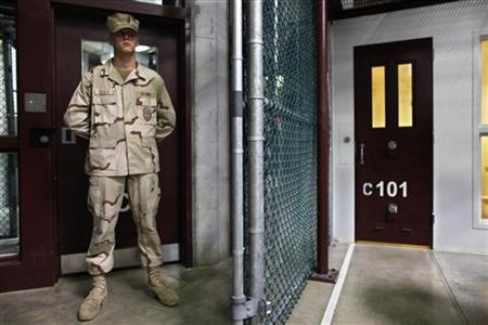 In this photo, reviewed by the U.S. military, a Guantanamo guard stands inside a doorway at Camp 6 detention facility at Guantanamo Bay U.S. Naval Base, Cuba, May 31, 2009. REUTERS/Brennan Linsley/Pool