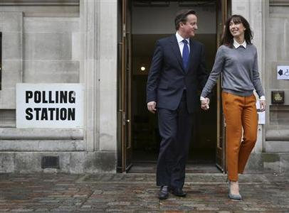 Britain's Prime Minister David Cameron walks from a polling station after voting in local elections with his wife Samantha (R) in central London May 3, 2012. REUTERS/Peter Macdiarmid