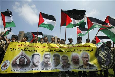 Palestinian scouts wave their national flags behind a banner depicting portraits of Palestinian prisoners during a protest in solidarity with them, who are on hunger strike against Israel's jail policies, in front of the U.N. headquarters offices in Beirut May 11, 2012. REUTERS/Sharif Karim