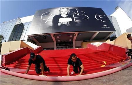Workers install the red carpet in front of the main entrance of the Festival Palace for the opening ceremony of the 65th Cannes Film Festival May 16, 2012. REUTERS/Eric Gaillard