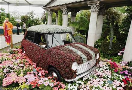 A man passes a mini covered in flowers on the Birmingham City Council stand during the press day at the Chelsea Flower Show in London May 21, 2012. REUTERS/Luke MacGregor