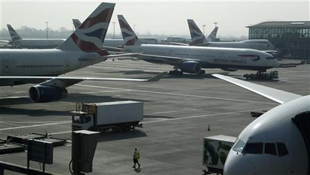 An airport worker walks across the apron past British Airways aircraft at Heathrow airport's Terminal 5 in London March 30, 2012. REUTERS/Phil Noble
