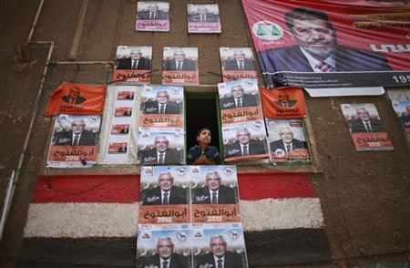 A boy looks out of a window covered with posters of presidential candidate Abdel Moneim Abol Fotouh in Cairo during presidential elections, May 23, 2012. REUTERS/Suhaib Salem