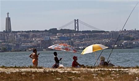 People relax in front of Lisbon's Seixal beach August 14, 2011. REUTERS/Hugo Correia