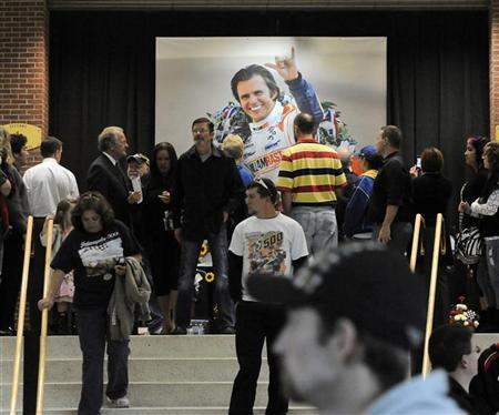 Fans stand at one of the memorial stands featuring IndyCar driver Dan Wheldon after the driver's memorial service in Indianapolis October 23, 2011. REUTERS/Tom Russo
