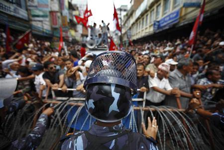 A riot police officer stands in front of barricades as members of the Brahmin-Chhetri Society try to enter a restricted area while marching towards the constitution assembly building to protest against federalism in Kathmandu, May 27, 2012, as the midnight deadline of the nation's first federal constitution approaches. REUTERS/Navesh Chitrakar